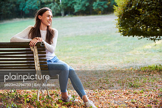 Smiling young woman sitting on bench in park - p623m2294793 by Eric Audras