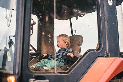 Kleiner Junge spielt in einem Traktor - p1046m1220961 von Moritz Küstner