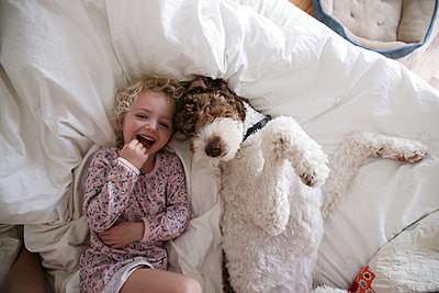 High angle portrait of cheerful girl relaxing with dog on bed at home - p1166m1230398 by Cavan Images