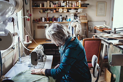 Senior female owner using sewing machine at workshop - p426m1543001 by Maskot