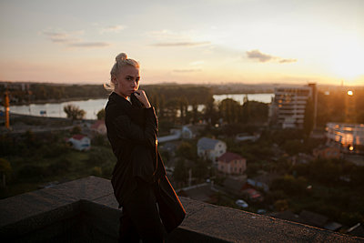 Pensive Caucasian woman standing on roof at sunset - p555m1523077 by Mykhailo Lukashuk