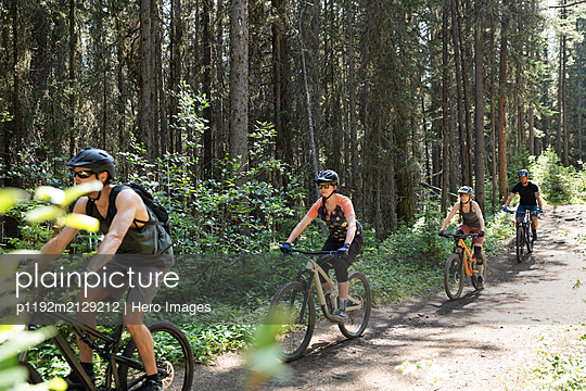 Friends mountain biking on trail in sunny woods - p1192m2129212 by Hero Images
