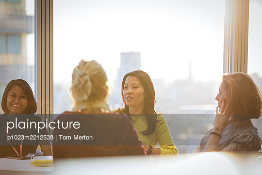 Businesswomen talking in conference room meeting - p1023m2212538 by Tom Merton