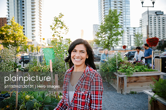 Portrait happy woman in urban community garden - p1192m2130131 by Hero Images