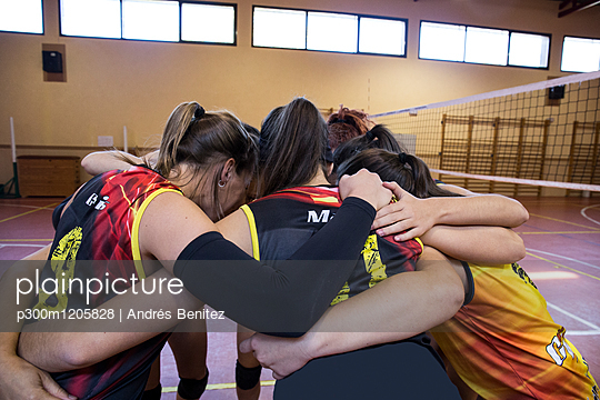 Female volleyball team huddling