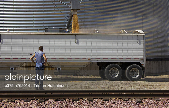 Man watching grain fall - p378m762014 by Tristan Hutchinson