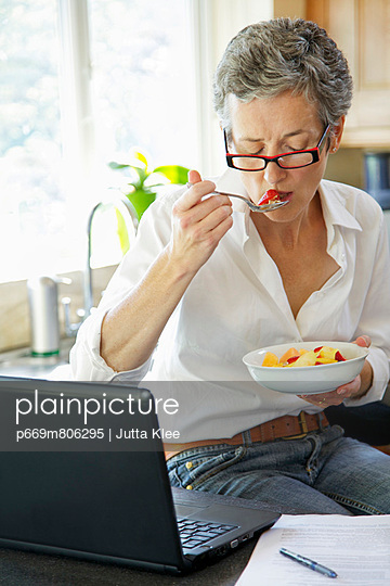Woman Eating Fruit Salad and Using Laptop - p669m806295 by Jutta Klee photography