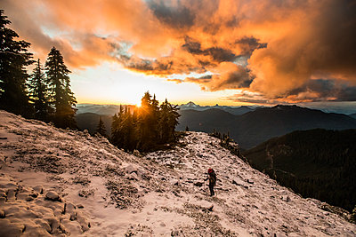 Backpacker hikes over snow on rocky mountain ridge. - p1166m2255898 by Cavan Images