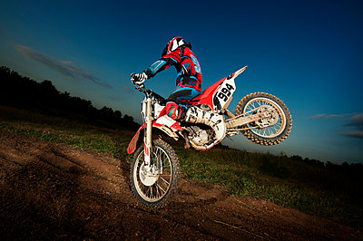Man performing stunt with dirt bike on field at dusk - p1166m969513f by Cavan Images