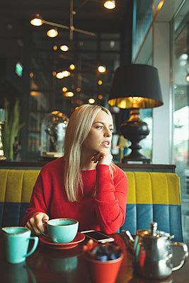 Woman looking away in cafeteria - p1315m2056344 by Wavebreak
