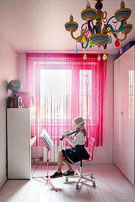 Girl sitting at the window at home playing violin - p300m2102891 by Ekaterina Yakunina