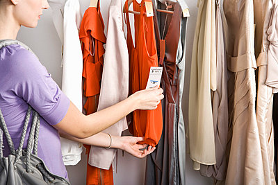 A woman looking at the price tag of a top on a clothing rail - p3019344f by Paul Hudson