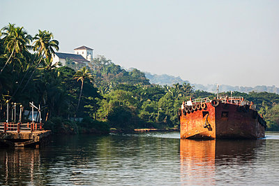 India, Cargo barge on the Mandovi River with Chapel of St Catherine in background; Old Goa - p442m840248 by James Sparshatt