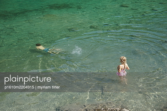 A brother and sister swim and play in a lake  - p1610m2204915 by myriam tirler