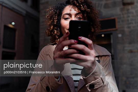 Woman using cell phone in an alley - p300m2103516 by Francesco Morandini