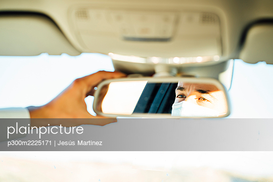 Man adjusting rear-view mirror in car - p300m2225171 by Jesús Martinez