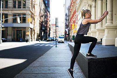 Female athlete exercising at sidewalk in city - p1166m1403676 by Cavan Images