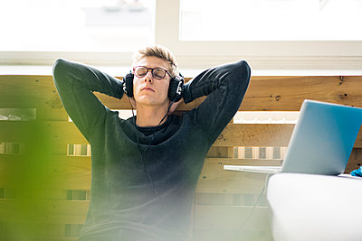 Relaxed young man sitting on the floor listening to music with headphones - p300m2083848 von Robijn Page