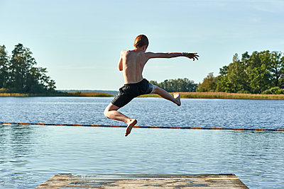 Redhead boy jumping into lake against clear sky - p300m2214090 by Jess Derboven