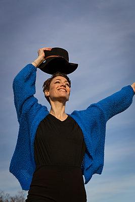 Frau mit Hut steht zufrieden auf Hausdach - p432m2248692 von mia takahara