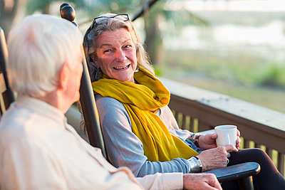 Older Caucasian couple drinking coffee on porch - p555m1413798 by Marc Romanelli
