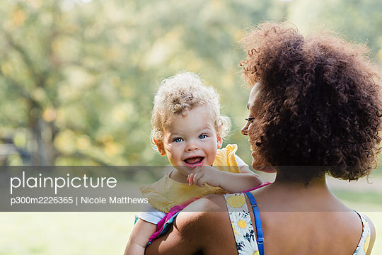Mother carrying smiling baby while standing at park - p300m2226365 by Nicole Matthews