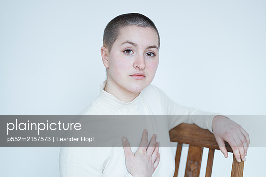 Young woman sitting on chair, portrait - p552m2157573 by Leander Hopf