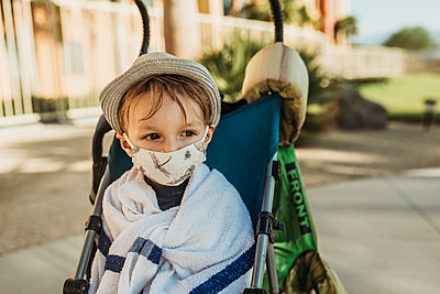Close up portrait of young boy with mask on outside on vacation - p1166m2218275 by Cavan Images