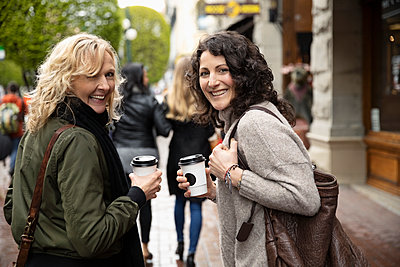 Portrait smiling, confident women friends with coffee walking on city sidewalk - p1192m1583373 by Hero Images