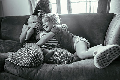 Mother and Young Children Embracing and Laughing on the Sofa - p1238m1042069 by Amanda Voelker