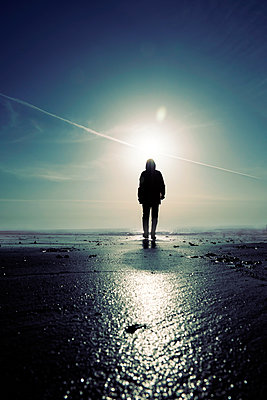 Rearview man in hooded anorak walking on beach at sunrise - p597m2186041 by Tim Robinson