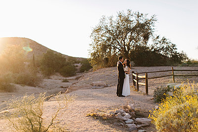 Bride and groom, in arid landscape, standing face to face - p924m1422652 by Jennifer van Son