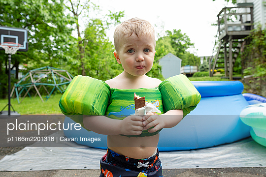 Young boy wearing swimming gear stands eating candy in yard with pool - p1166m2201318 by Cavan Images