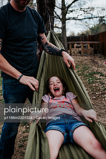 Dad pushing happy girl in hammock - p1166m2201334 by Cavan Images