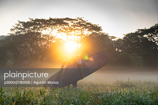 Back view of young surfer on the way to the beach at sunrise, Costa Rica - p300m2180006 by Agustin Munoz