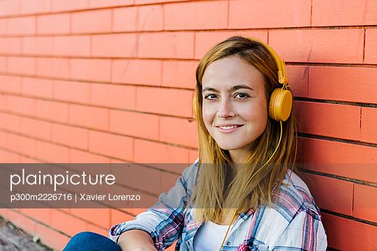 Smiling woman listening music through headphone sitting against brick wall - p300m2226716 by Xavier Lorenzo
