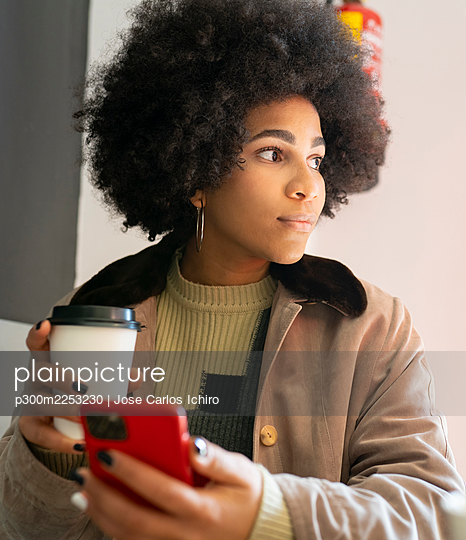 Curly hair woman with coffee cup using mobile phone while sitting at cafe - p300m2253230 by Jose Carlos Ichiro