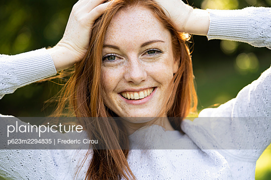 Portrait of smiling young woman in park - p623m2294835 by Frederic Cirou