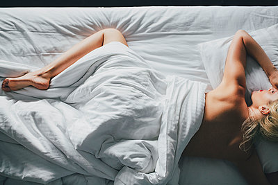 Overhead view of sensuous woman lying on bed at home - p1166m1163662 by Cavan Images