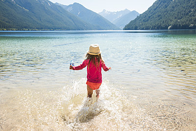 Rear view of toddler girl running into Chilliwack Lake, B.C., Canada. - p1166m2212445 by Cavan Images
