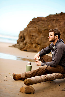 Side view of man looking away while sitting on wood at beach - p1166m969437f by Cavan Images