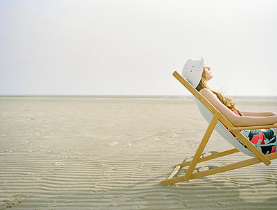 Woman on beach relaxing in canvas chair - p1207m1111697 by Michael Heissner