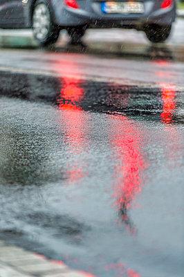 Germany, mirrored red light of traffic light on rain-wet road, rear lights of car - p300m2079966 by Frank Röder