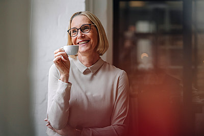 Smiling mature businesswoman having a coffee break at the window in office - p300m2156079 by Gustafsson