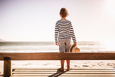 Rear view of boy with hat standing on the beach - p300m2167550 by Floco Images