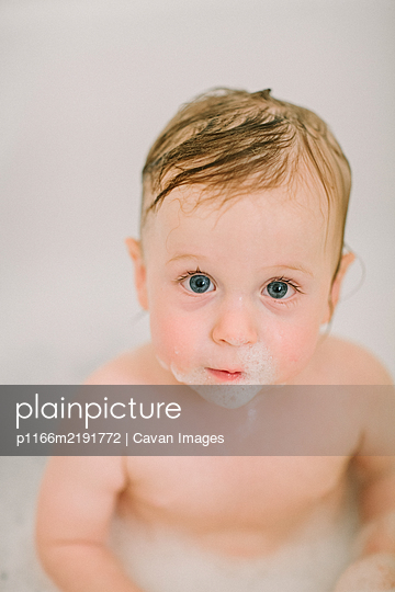 Closeup of baby in the bathtube with bubbles on face - p1166m2191772 by Cavan Images