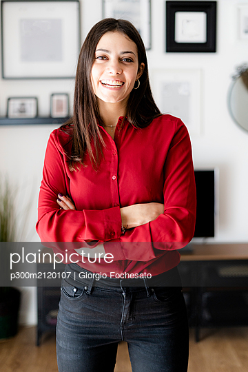Portrait of happy young businesswoman at home - p300m2120107 by Giorgio Fochesato