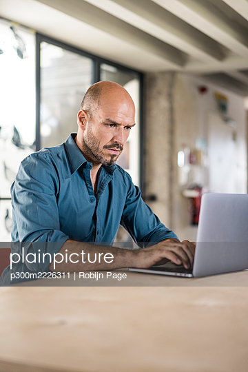 Businessman working on laptop while sitting by table at office - p300m2226311 by Robijn Page