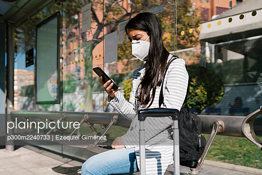 Woman waiting for bus while using smart phone on sunny day during COVID-19 pandemic - p300m2240733 by Ezequiel Giménez