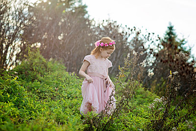 Girl wearing wreath while standing amidst plants on field at park - p1166m1544984 by Cavan Social